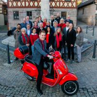 Gruppenbild der Kandidatinnen und Kandidaten auf der Liste der SPD mit Bürgermeisterkandidat Maximilian Lindner an der Spitze auf dem Roller.